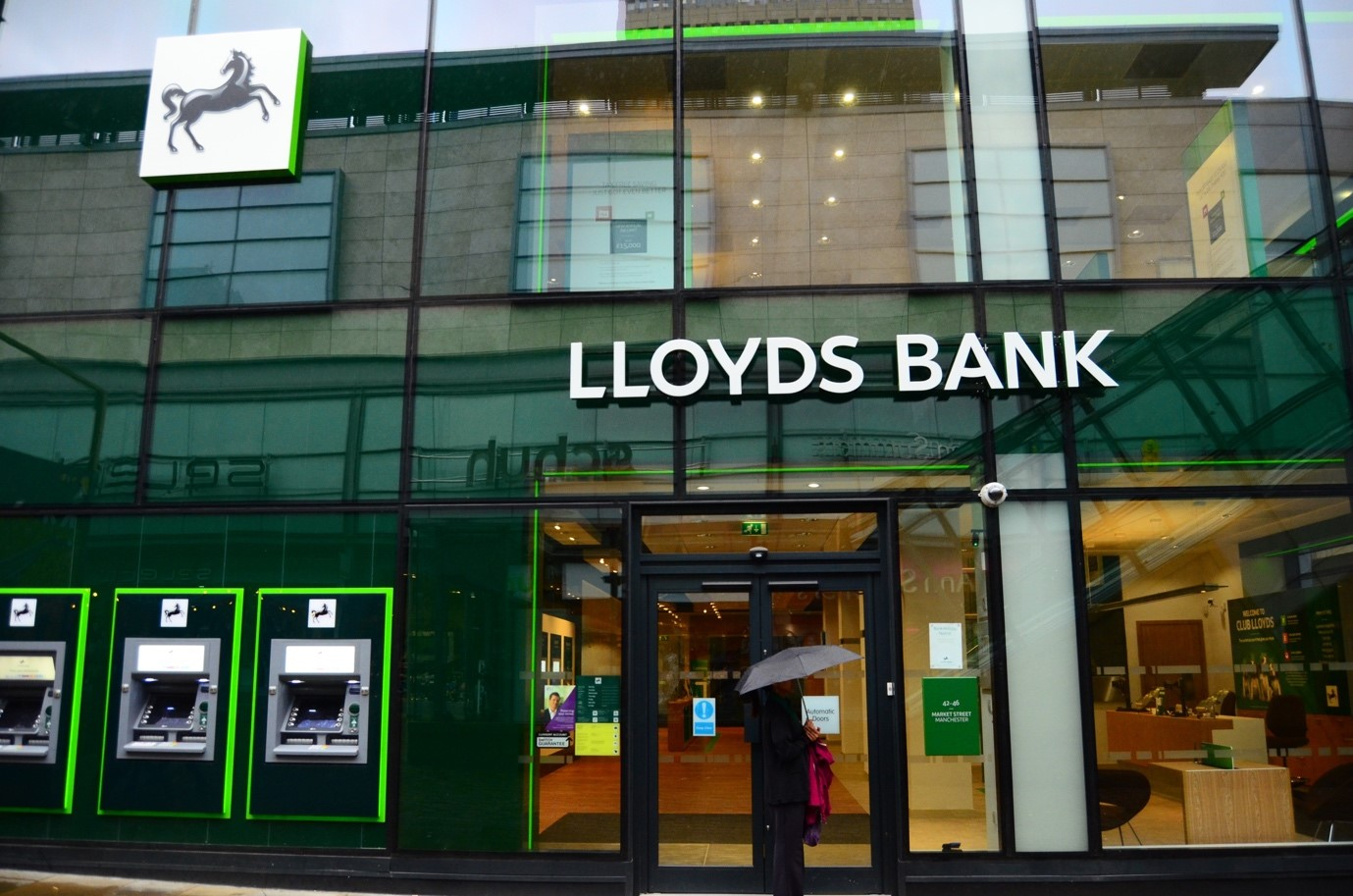 The front of a Lloyds bank branch. A person stands outside the doors under an umbrella.