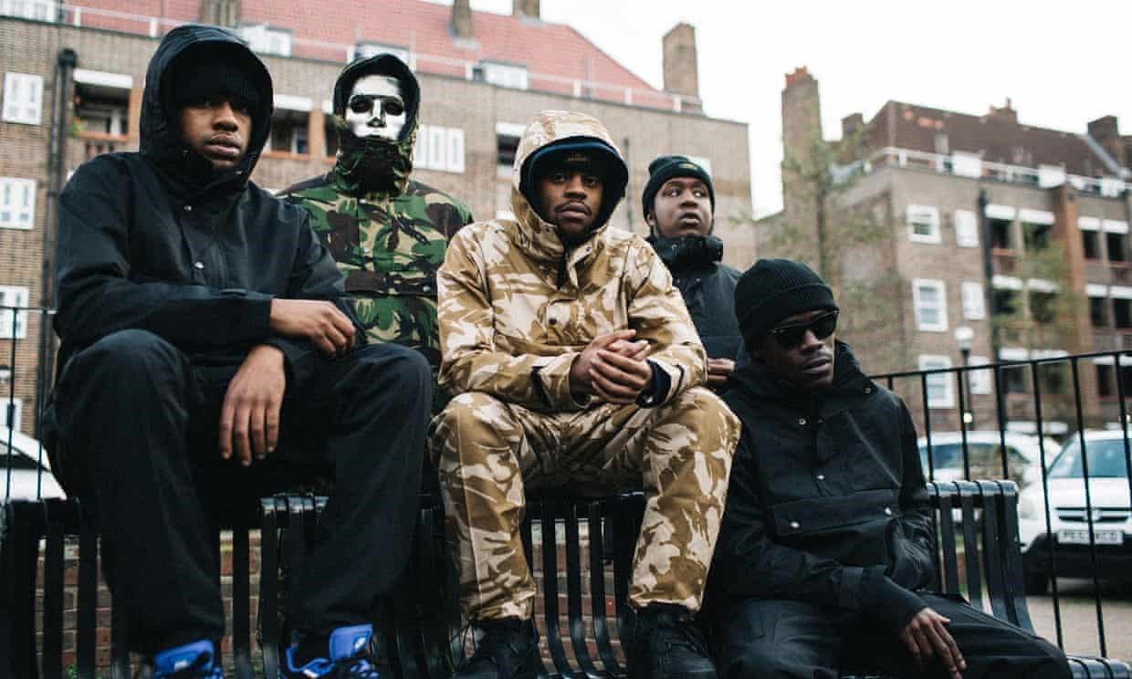 Four young black men sit together on a bench. They are dressed casually wearing tracksuits, hoodies and wool hats. One of the men wears sunglasses. One man stands at the back wearing a silver mask.