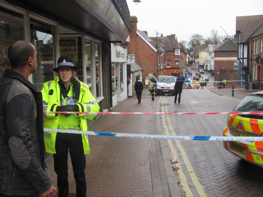 A female police officer stands at a police cordon set up on a street. There is a man standing on the other side of the cordon opposite her with his back to the camera. In the distance there is a police van and beyond that a police car.