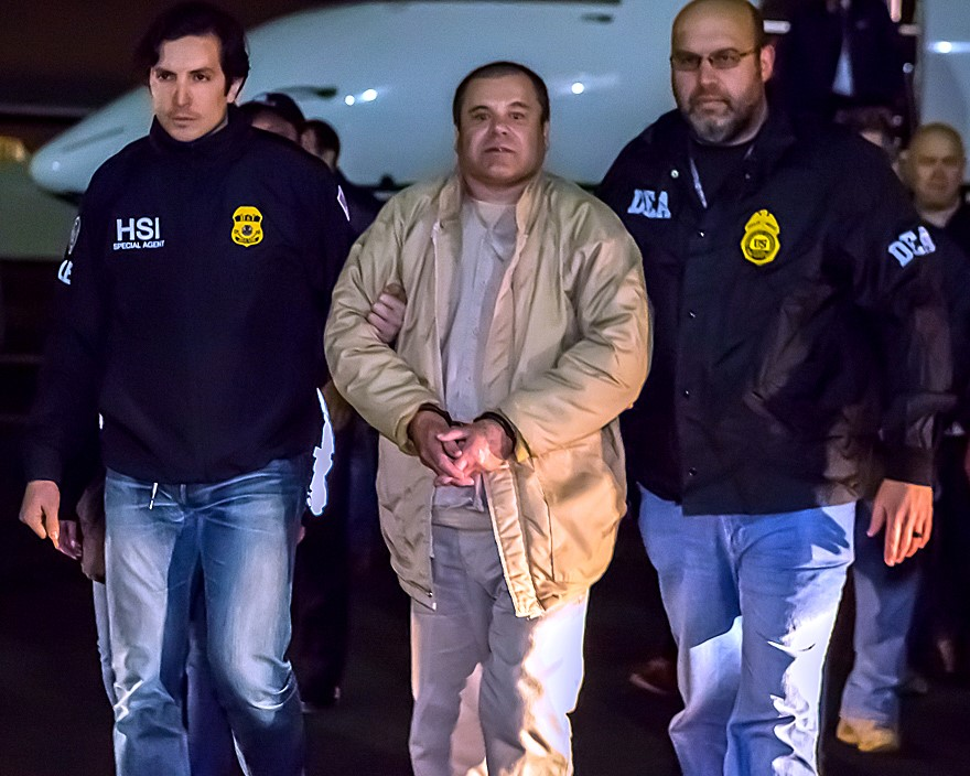 Mexican drug lord El Chapo being escorted by authorities. He is handcuffed.
