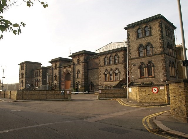 A picture of the exterior of HMP Wandsworth prison, London. It is a large brick building with a huge wooden door.