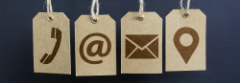 An image of four icons printed on brown paper tags against a dark blue background. The first icon is a telephone handset, the second is an @ symbol, the third is an envelope (email), and the last is a location pin.