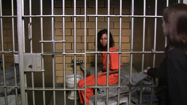 A woman prisoner with olive skin and shoulder-length wavy dark brown hair, wearing an orange overall sits on a bed in a small prison cell.