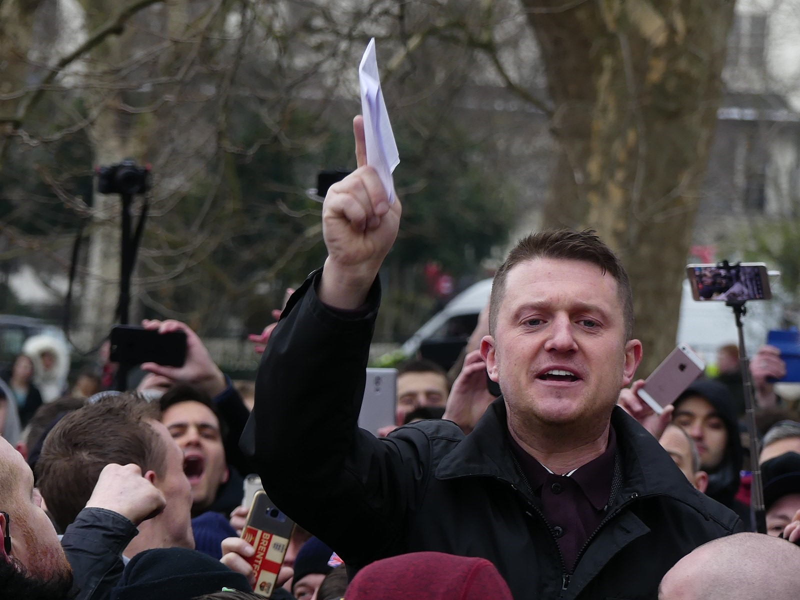 A picture of right-wing activist and politician Tommy Robinsonstanding amongst a crowd of people, many of whom are using their phones to film/take pictures of him