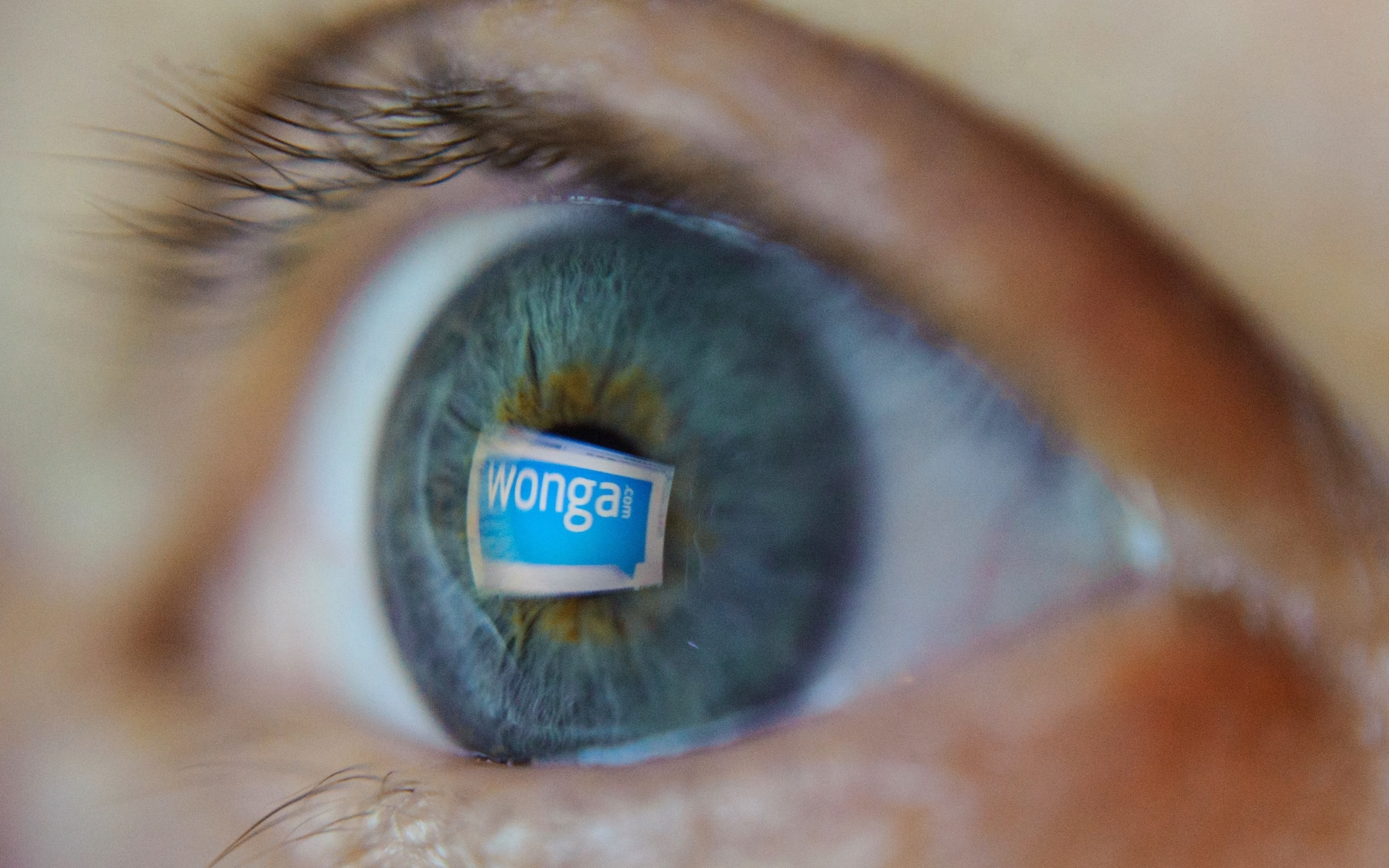 A close up of a person's blue eye with a Wonga logo reflected in it