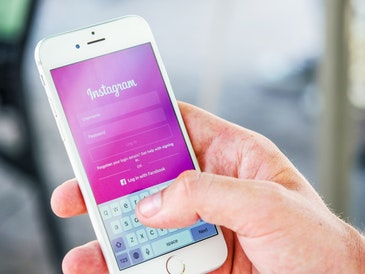 A close-up image of a hand holding a white Apple mobile phone. The Instagram login screen is displayed on the phone.