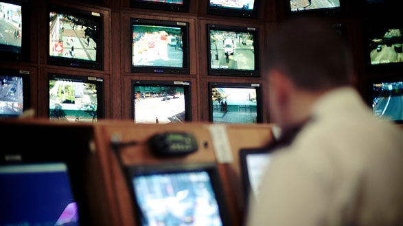 A CCTV operator in front of a series of screens monitoring Birmingham city centre