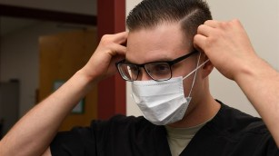 A person in glasses putting on a face-mask
