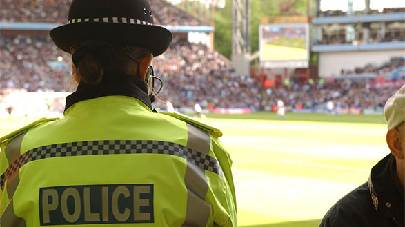 Police officer standing with their back to the camera in a hi-viz jacket with the word police on the back. There is a football pitch and crowd in the background