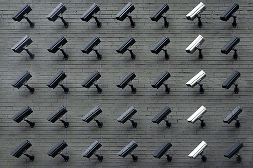 Lines of security cameras arranged on a brick wall