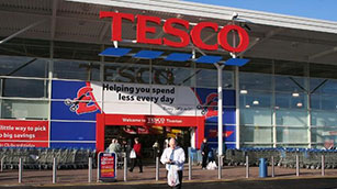 Front of a Tesco Superstore with man walking with a shopping bag through the car park